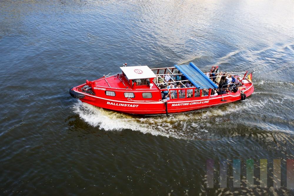 """Die knallrote Barkasse """"Ballinstadt"""" der Maritime-Circle-Line befördert Touristen und Hamburger auf einem Rundkurs durch den Hamburger Hafen und läuft dabei mehrere Anleger an - zum Beispiel in der Speicherstadt oder auf der Veddel"""