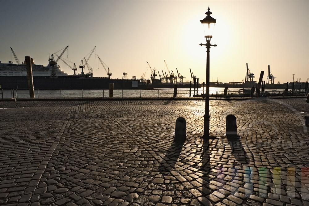 Blick vom Hamburger Fischmarkt mit historischer Strassenlaterne auf ein im Dock bei Blohm & Voss liegendes Kreuzfahrtschiff, sonniges  Gegenlicht
