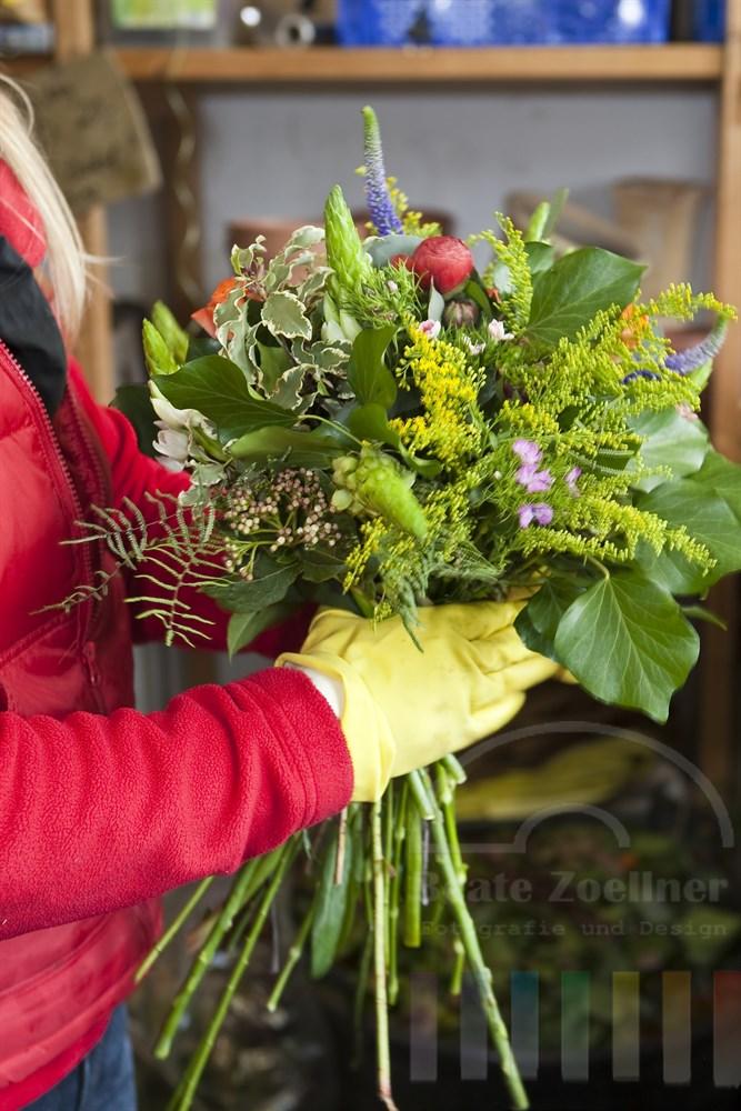 Floristen-Haende binden bunten Blumenstrauss