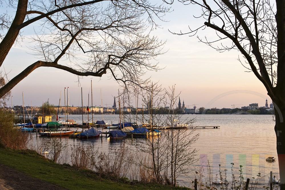 Abendstimmung: Segelboote liegen vertäut am Bootsteg an der Aussenalster - im Hintergrund die Türme der Hansestadt Hamburg