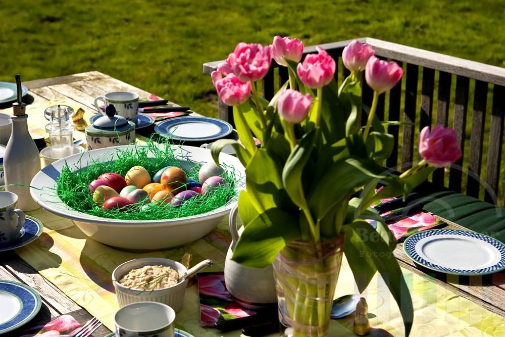 gedeckter Gartentisch im Freien mit Osterdekoration und Frühlings-Tulpen