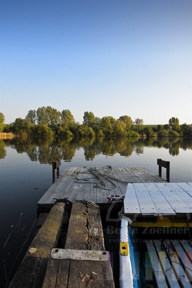 Ruderboot liegt an einem morschen Holzsteg am See, Abendstimmung, sonnig