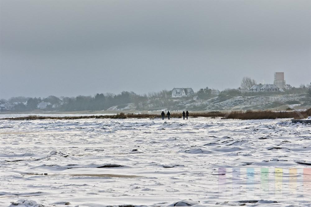 Urlauber spazieren an der winterlichen Wattenmeerküste zwischen Keitum und Munkmarsch auf Sylt