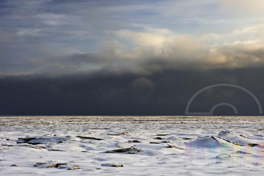 vereistes Wattenmeer vor Sylt mit Schneedecke und Wolkenhimmel, sonnig