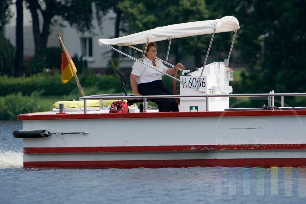 Frau in Uniform steuert Ausflugsschiff bei herrlichem Sommerwetter über die Hamburger Aussenalster