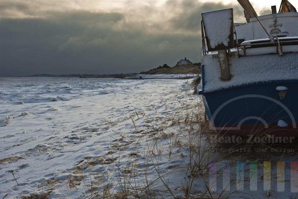 Schnee und Eis bedecken Wattenmeer und Strand in Munkmarsch/Sylt. Ein Segelboot liegt verlassen am Ufer, sonniges Gegenlicht
