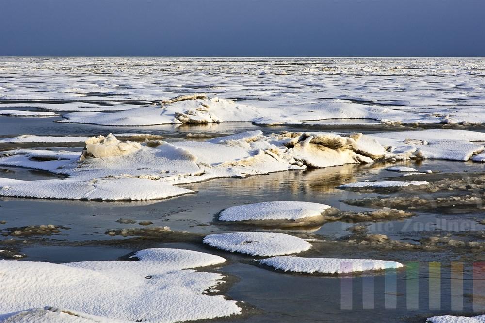 auflaufendes Wasser bricht sich seinen Weg durch das Eis am Sylter Wattenmeer, sonnig