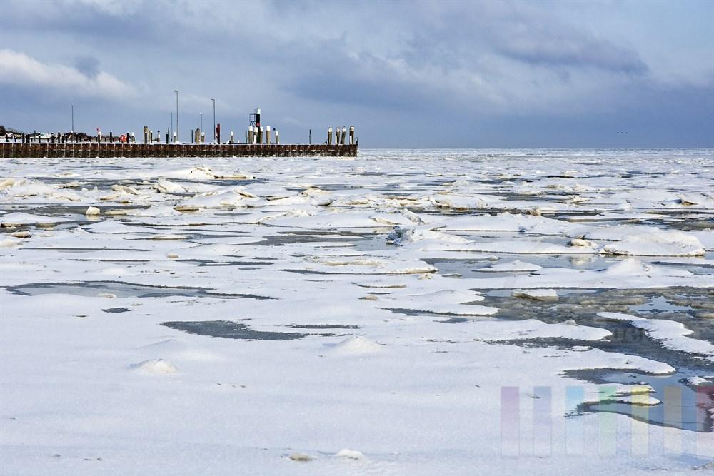 vereistes Wattenmeer am Munkmarscher Hafen mit Schneedecke