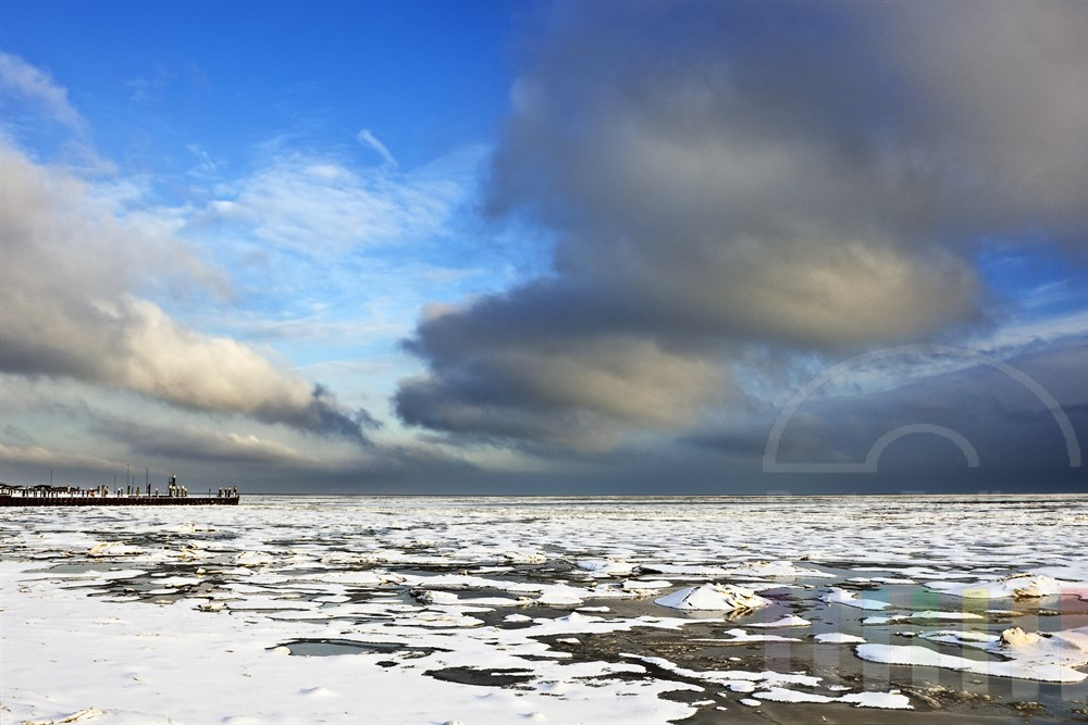 vereistes Wattenmeer vor dem Hafen von Munkmarsch/Sylt mit Schneedecke, blauer Himmel und sonnig