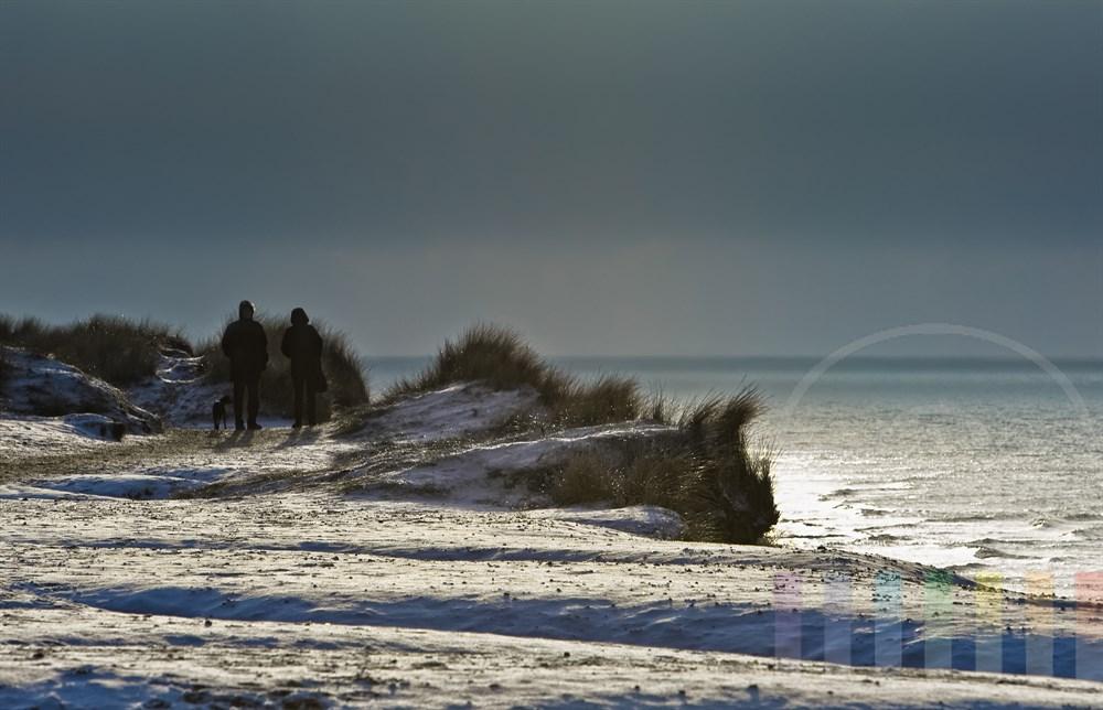 warm gekleidetes Urlauberpaar mit Hund steht auf dem verschneiten Roten Kliff in Kampen und schaut auf die Nordsee