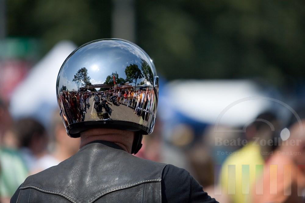 Menschenmenge und Motorräder spiegeln sich in einem blank polierten Motorradhelm