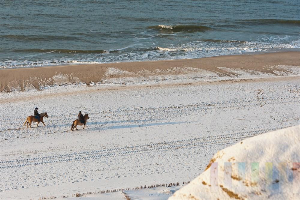 zwei Reiterinnen auf Pferden am verschneiten Strand von Kampen/Sylt unterhalb des Roten Kliffs, sonnig