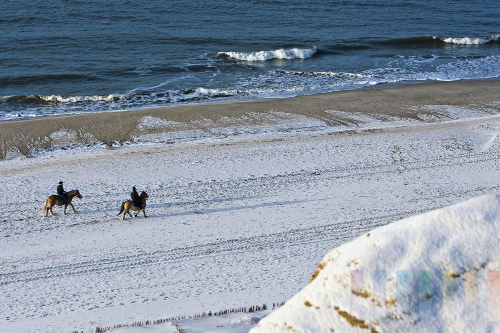 zwei Reiter am verschneiten Nordseestrand von Kampen/Sylt unterhalb des Roten Kliffs