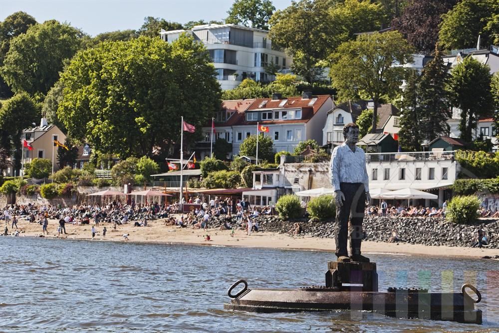 """Figur des zeitgenoessischen Bildhauers Stephan Balkenhol steht auf auf einem Schwimmponton in der Elbe vor Hamburg-Oevelgoenne - im Hintergrund buntes Treiben an der Kult-Kneipe """"Strandperle"""", sommerlich"""