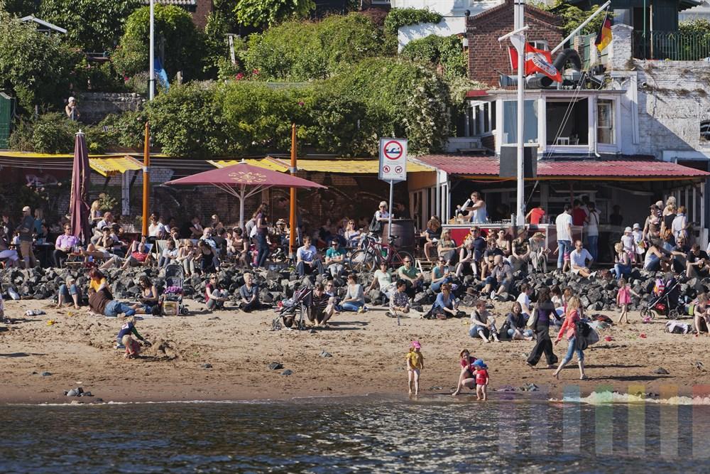 """Sommer in  Hamburg: Einer der beliebtesten Treffpunkte in der Hansestadt ist bei Sonnenschein die Kultkneipe """"Strandperle"""" am Elbufer in Oevelgoenne - fotografiert von der Wasserseite"""