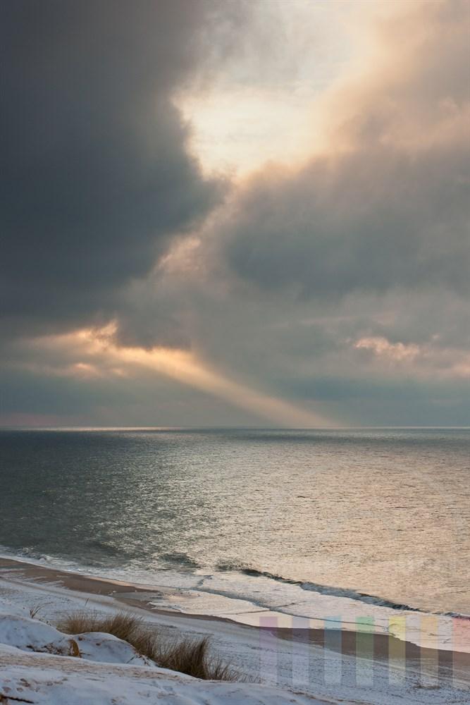 Blick vom Roten Kliff in Kampen/Sylt auf die Nordsee und den Wolkenhimmel, durch den sich ein Lichtrahl auf die Wasseroberflaeche draengt, winterlich