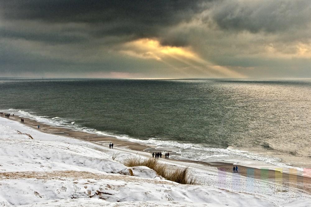 Blick vom verschneiten Roten Kliff in Kampen auf den Strand und die Nordsee - wenige Sonnenstrahlen durchdringen die Wolkendecke und scheinen auf das Meer