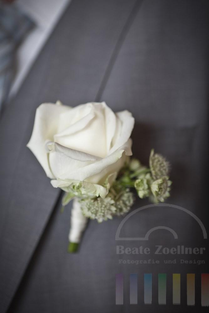 weiße Rose steckt am Anzug-Revers eines Braeutigams