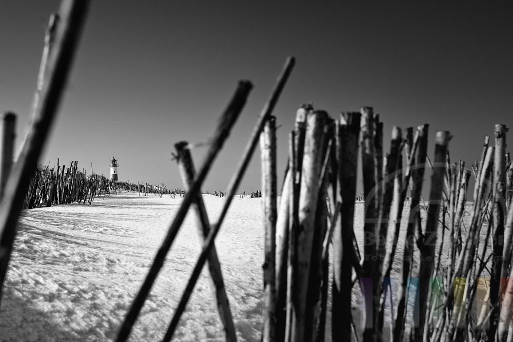 Der Leuchtturm Ellenbogen-West im Winter, der Strand liegt unter einer dicken Schneedecke - im Vordergrund Reisig, der dem Küstenschutz dient