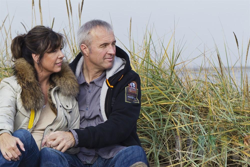 Mann und Frau (40+) sitzen im Duenengras auf Sylt und schauen auf die Nordsee