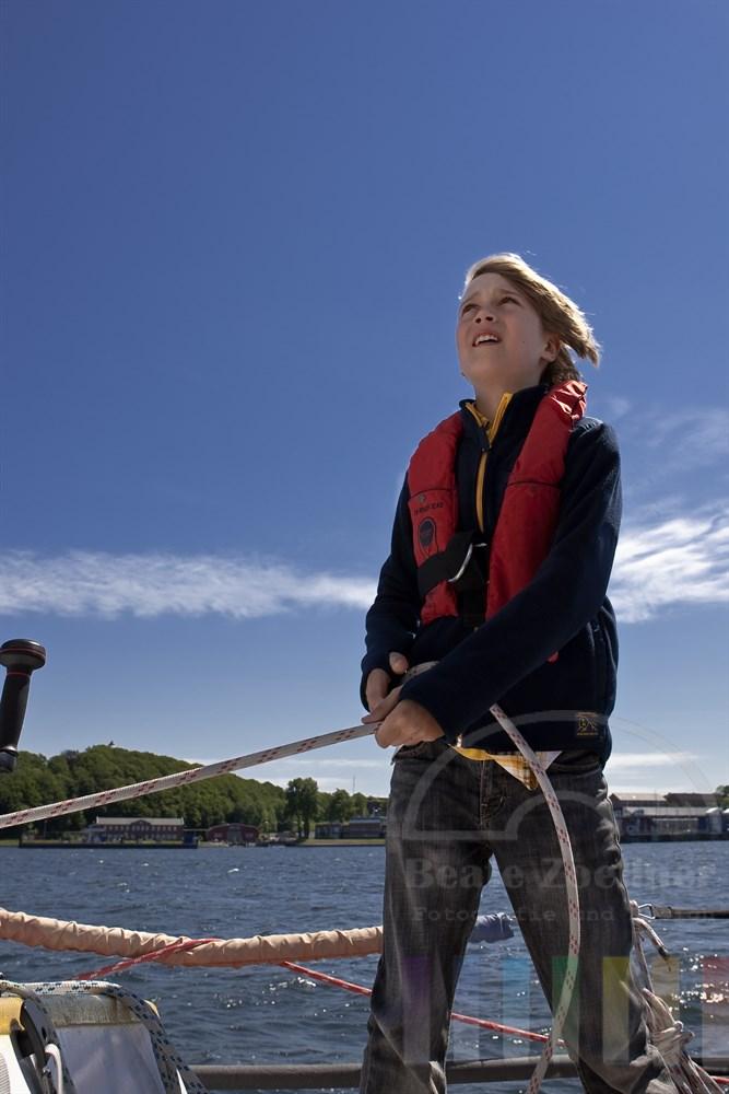 10jähriger Junge steht an Deck einer großen Segelyacht und hält eine Schot in den Händen. Dabei blickt er konzentriert auf Mast und Segel der Yacht