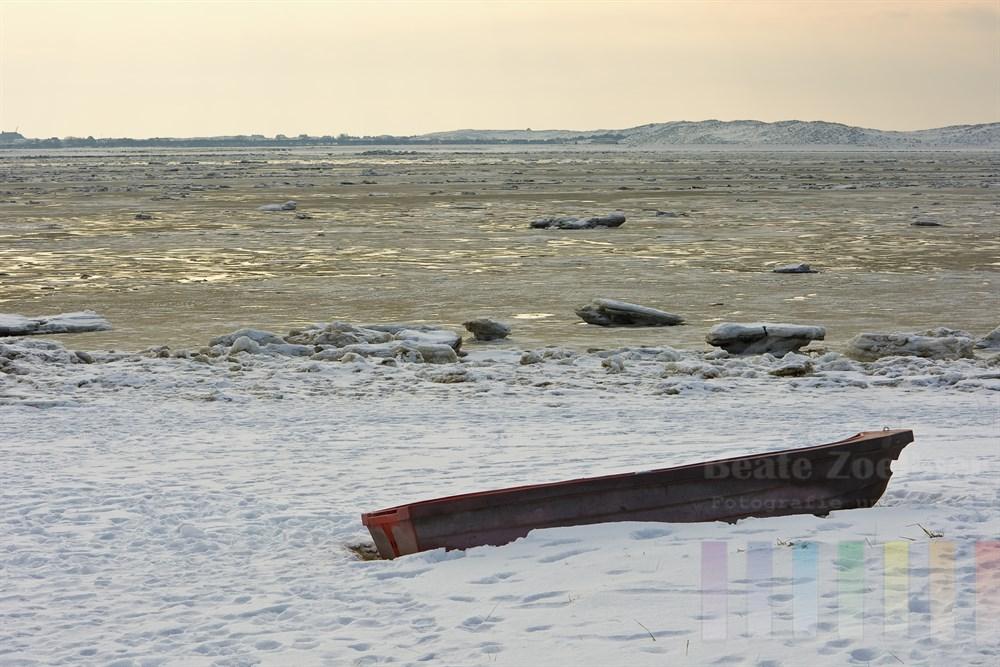 Winter am Königshafen in List/Sylt. Am verschneiten Strand liegt ein verlassenes Ruderboot
