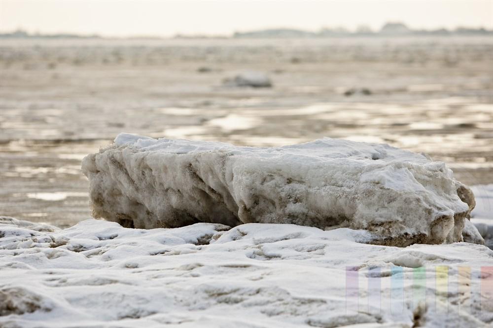 großer Eisblock liegt im diffusen Sonnenlicht am Strand des Lister Königshafens. Im Hintergrund die Ortschaft List