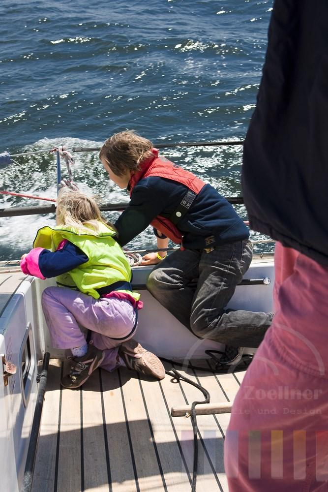kleines Mädchen (6 Jahre) und Junge (10) - sie sind Geschwister - sitzen an der Reling und geniessen Wind und Wasser. Beide Kinder tragen Schwimmweste. Im Anschnitt der Vater, der die beiden nicht aus dem Augen lässt