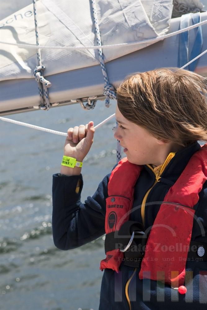 Segeltörn-Impression: 10jähriger Junge mit Schwimmweste schaut verträumt  auf´s Wasser und hält sich mit einer Hand an einem Tau am Baum des Grosssegels fest