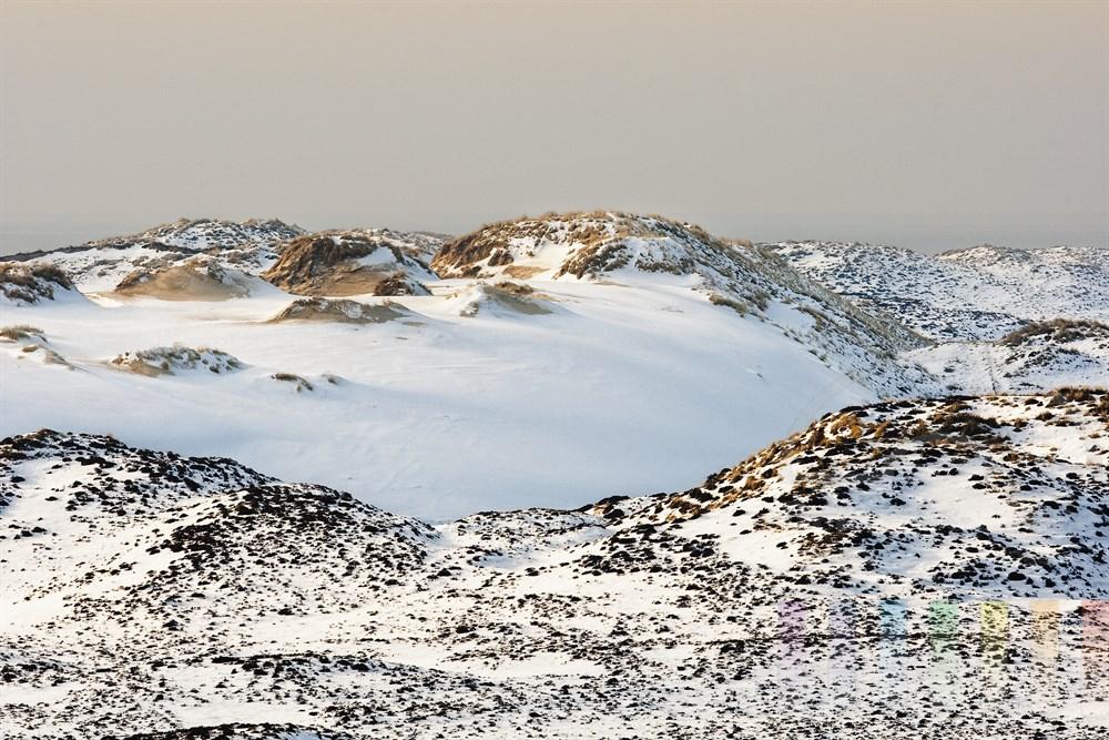 Blick über die verschneiten und unberührten Sylter Wanderdünen bei List. Im dunstigen Hintergrund die Nordsee