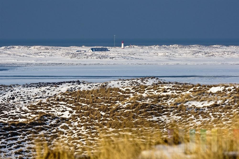 Blick aus den verschneiten Dünen auf den Sylter Ellenbogen und den Leuchtturm, sonnig