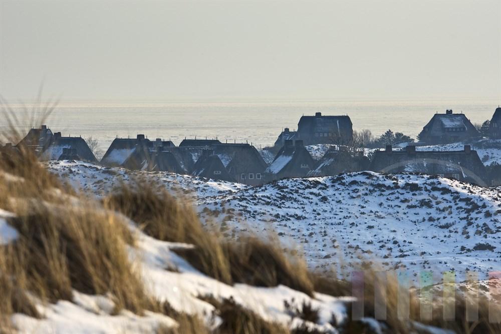 Blick aus den verschneiten Dünen auf die Reetdachhäuser der Ortschaft List und das vereiste Wattemeer