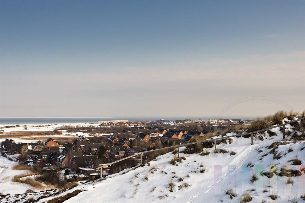 Blick aus den verschneiten Dünen auf die Ortschaft List und die Nordsee, sonnig