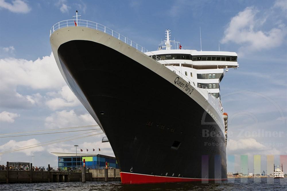 Das Kreuzfahrtschiff Queen Mary 2 liegt kurz vor ihrer Abreise nach Norwegen noch vertaeut am Kreuzfahrtterminal in der Hamburger Hafen City. Tausende Menschen warten am Ufer der Elbe auf das Ablegen, sommerlich