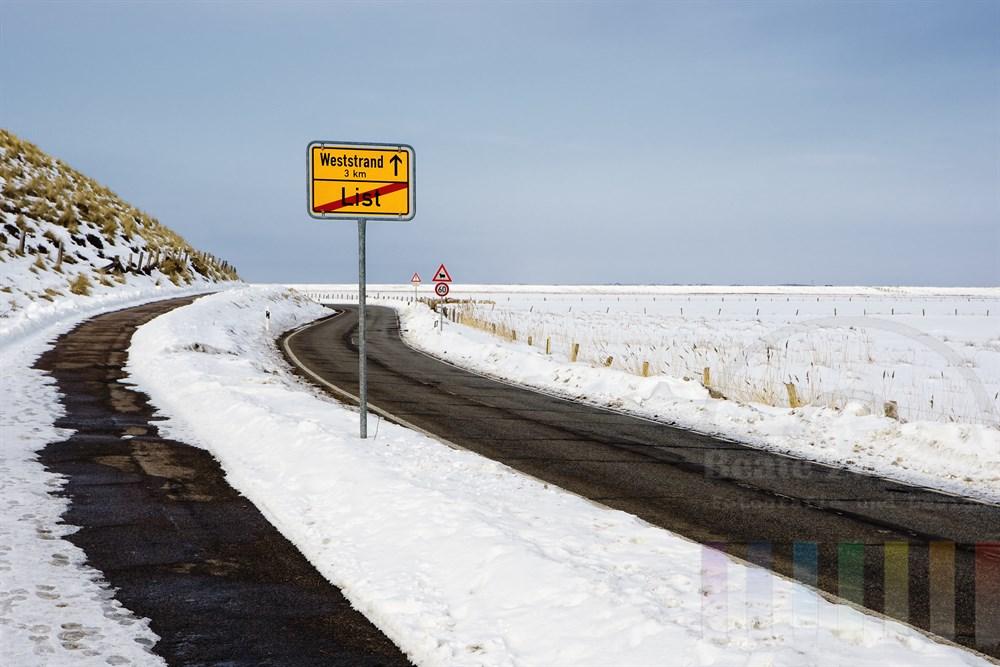 geräumte Strasse durch verschneite Sylter Landschaft von der Ortschaft List zum Weststrand der Insel