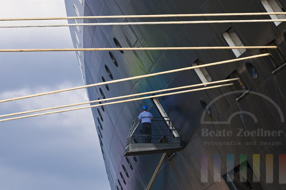 Besatzungsmitglied der QM2 steht an der Bordwand und ueberwacht das Ablegemanoever - noch halten dicke Taue das Kreuzfahrtschiff am Kai