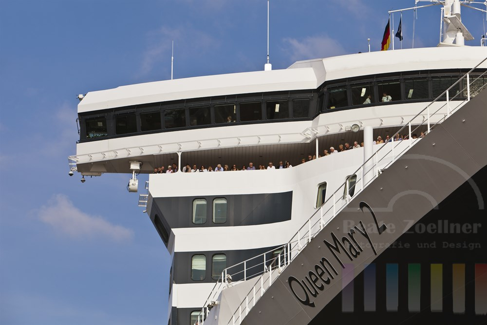 Passagiere stehen an Deck unterhalb der Bruecke der Queen Mary 2 und warten auf die Abfahrt des Kreuzfahrt-Riesen