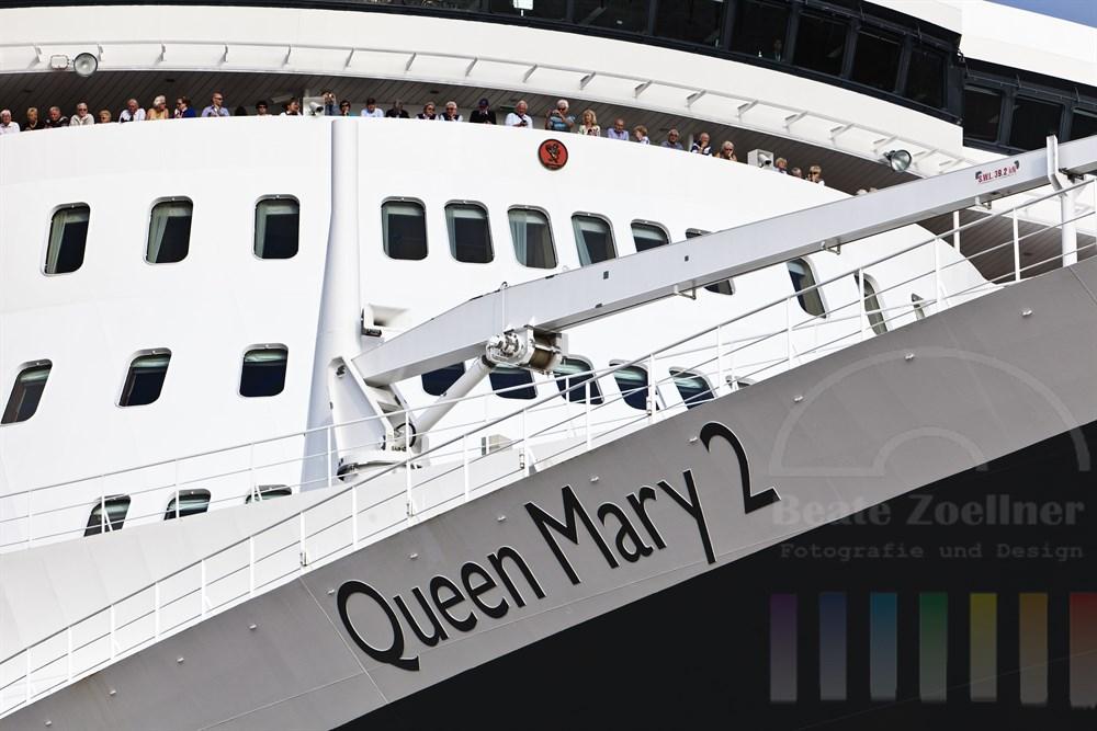 Das Kreuzfahrtschiff Queen Mary 2 (aus ungewoehnlicher Perspektive) kurz vor der Abreise - zahlreiche Passagiere stehen an Deck, sonnig