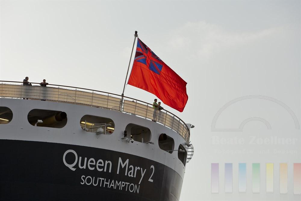 """Passagiere stehen an der Reling am Heck der """"Queen Mary 2"""" und warten auf das Ablegemanoever. Die britische Handelsflagge weht im Wind"""