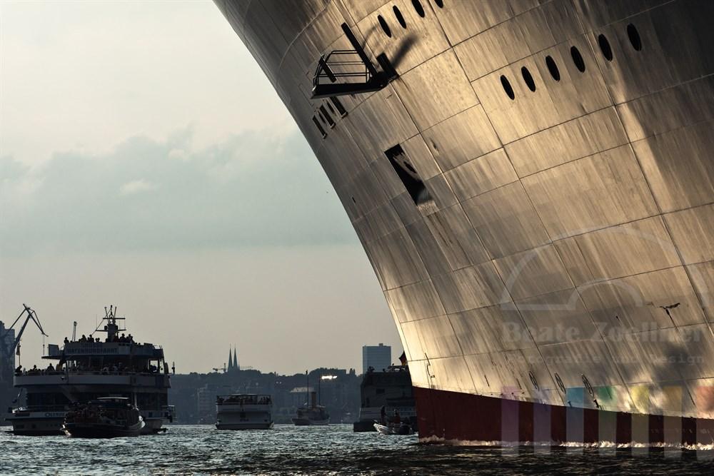 Das Kreuzfahrtschiff Queen Mary 2 liegt kurz vor ihrer Abreise nach Norwegen noch vertaeut am Kreuzfahrtterminal in der Hamburger Hafen City. Zahlreiche Boote und Schiffe mit Touristen und Schaulustigen warten auf die Abfahrt, sommerlich. Das Licht der Abendsonne spiegelt sich auf der Bordwand der QM2