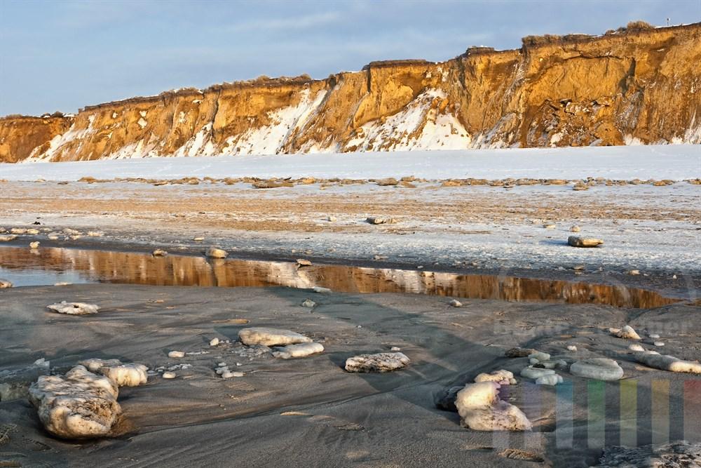 Von der Nordsee angespülte Eisbrocken liegen am Strand von Kampen vor dem verschneiten Roten Kliff, sonnig
