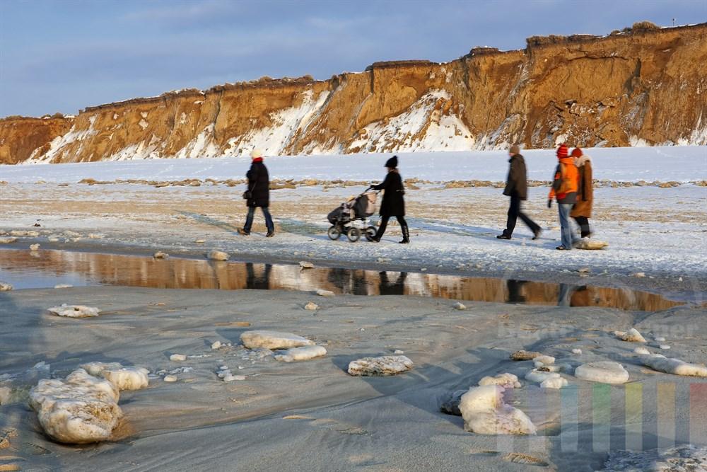 Spaziergänger am winterlichen Strand vor dem Roten Kliff in Kampen/Sylt