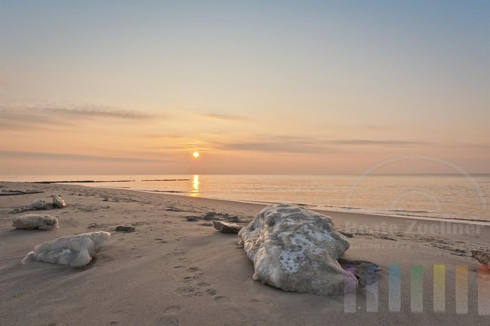 Dicke Eisbrocken liegen an einem windstillen Winter-Nachmittag am Strand von Kampen/Sylt. Die Sonne steht knapp ueber dem Horizont