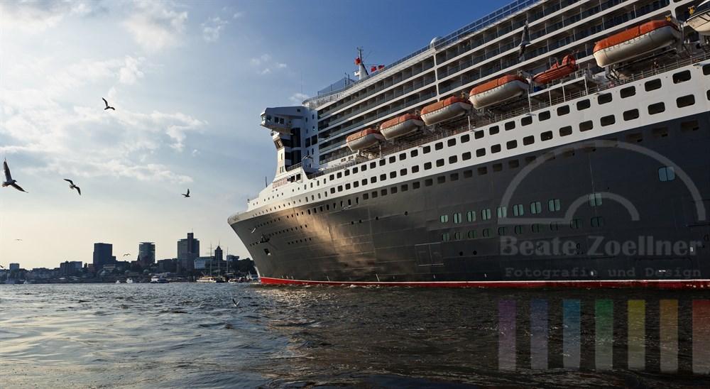 Das Kreuzfahrtschiff Queen Mary 2 liegt kurz vor ihrer Abreise nach Norwegen noch vertaeut am Kreuzfahrtterminal in der Hamburger Hafen City. Im Hintergrund die St. Pauli-Landungsbruecken