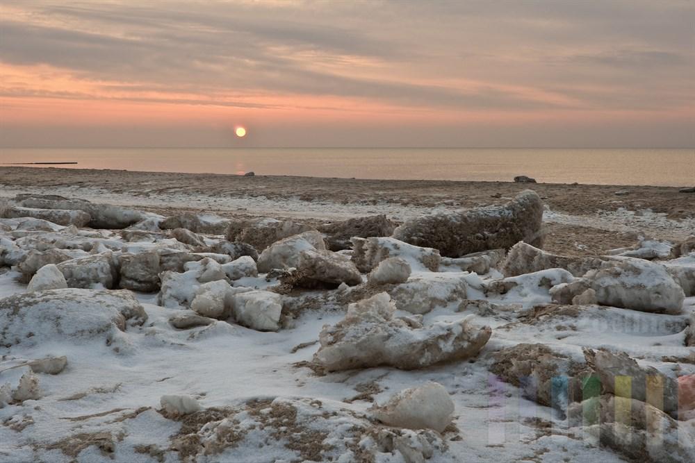 Sonnenuntergang über der Nordsee am mit Eisschollen bedeckten Strand von Kampen/Sylt
