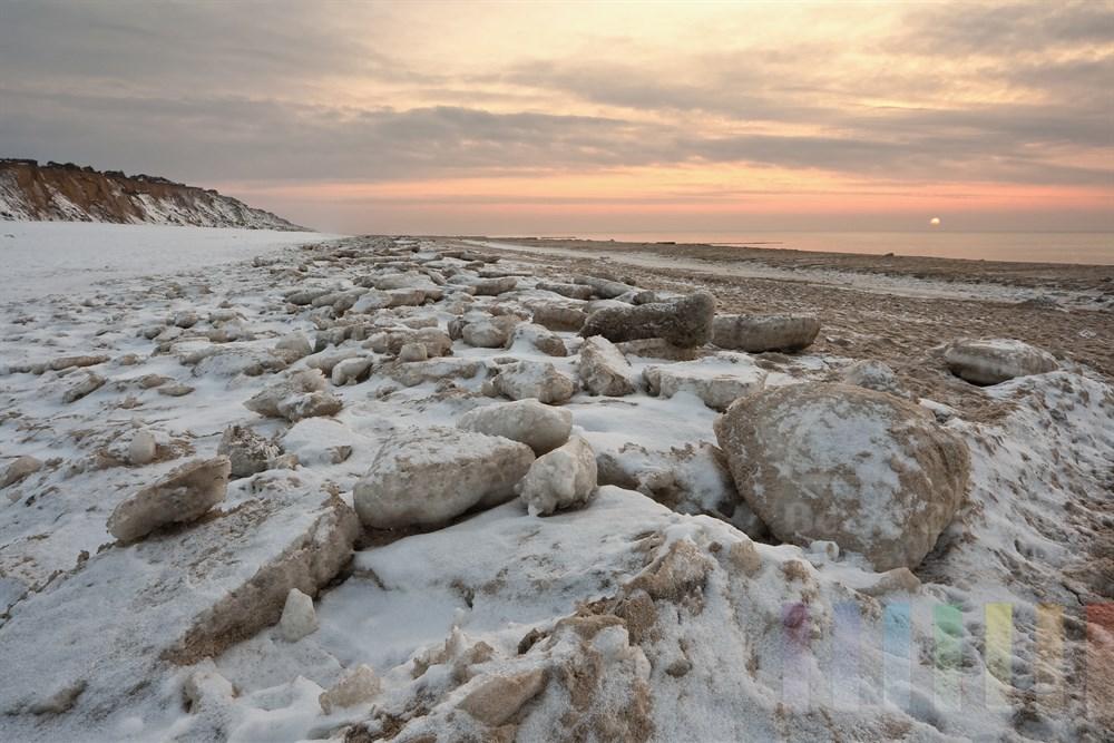 Sonnenuntergang über der Nordsee am mit Eisschollen bedeckten Strand vor dem Roten Kliff in Kampen/Sylt