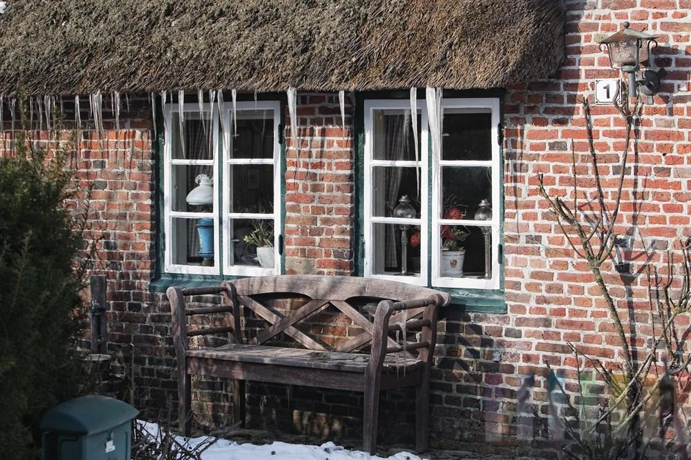 Eiszapfen haben sich am Reetdach eines historischen Reetdachhauses in Keitum gebildet, sonnig
