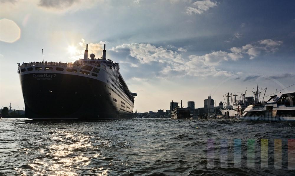 Das Kreuzfahrtschiff Queen Mary 2 laeuft aus dem Hamburger Hafen aus. Zahlreiche Passagiere stehen an Deck. Gegenlicht, Abendstimmung