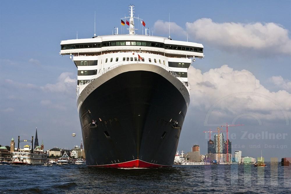 """Das Kreuzfahrtschiff """"Queen Mary 2"""" laeuft aus dem Hamburger Hafen aus, zahlreiche kleine Schiffe begleiten den Luxusliner. An Deck stehen winkende Passagiere. Im Hintergrund die Baustelle der Elbphilharmonie und die Hamburger Landungsbruecken, sonnig"""