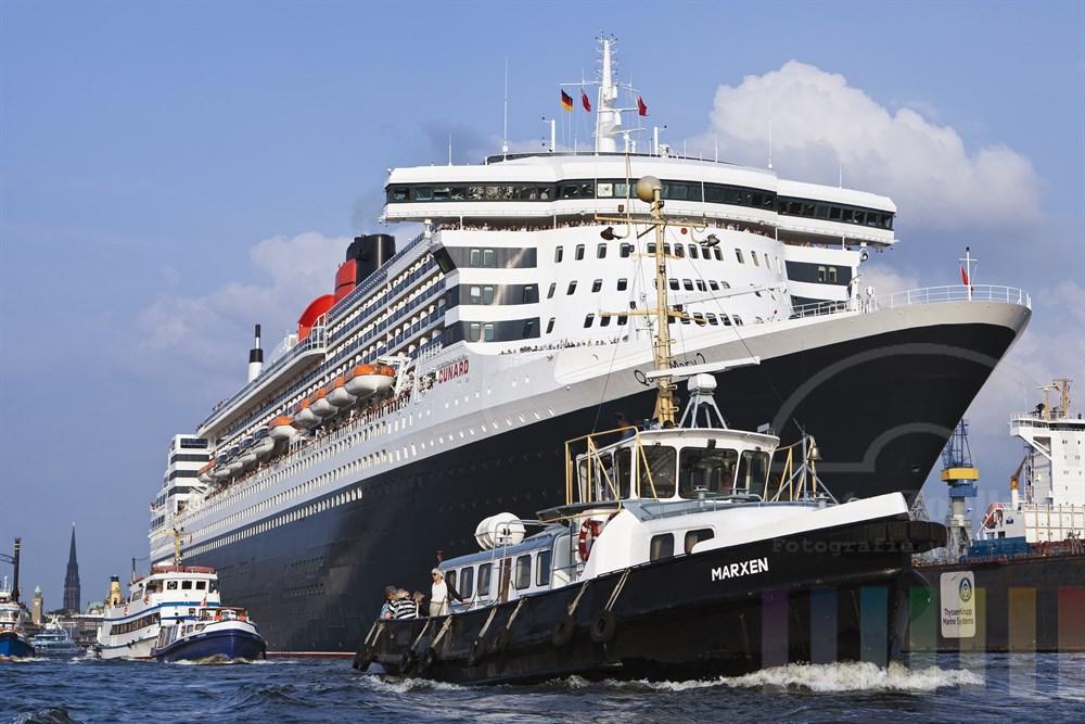 """Das Kreuzfahrtschiff """"Queen Mary 2"""" laeuft aus dem Hamburger Hafen aus, zahlreiche kleinere Schiffe begleiten den Luxusline ein STueck auf seiner Reise. An Deck stehen winkende Passagiere, sonnig. Im Hintergrund der Pegelturm der Landungsbruecken und die Nikolaikirche"""